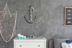 Ocean inspired interior. Modern ocean inspired  interior with white commode, fishing net and anchor hanging on the wall Stock Photos