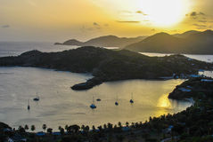 Ocean Island Harbor Sunset. The sun sets over the harbor of a mountainous island chain. Boats anchor in the harbor Stock Photography