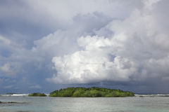 Ocean island w storm clouds royalty free stock image