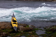 Ocean kayak beached on rocky shore at tidal rapids Stock Image