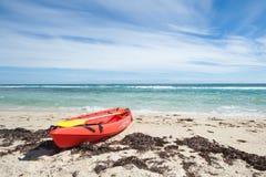 Ocean kayak. Red sea kayak on the beach in front of the ocean Stock Photos