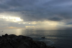 Ocean landscape at sunset. Light shining through the clouds from a rock outcrop Royalty Free Stock Image