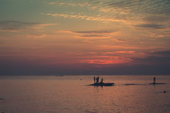 Ocean landscape at sunset. Silhouettes of fishermen. Big Game Fishing at sundown. Landscape of the ocean and sunset in the clouds. Unrecognizable people Royalty Free Stock Images