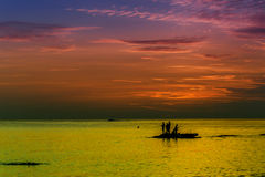 Ocean landscape at sunset. Silhouettes of fishermen. Stock Photo