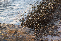 Ocean lapping on pebbles and rocks Stock Photo