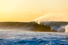 Large Wave Dawn Surfer. Photo image of distant unidentified surfer going over the wave with spray at dawn sunrise Royalty Free Stock Photography