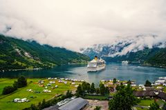 Ocean liner in village harbor. Ship in norwegian fjord on cloudy sky. Travel destination, tourism. Adventure, discovery. Geiranger, Norway - January 25, 2010 stock image
