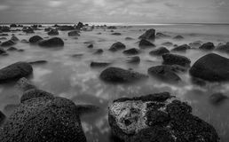 Ocean long exoosure. A moody long exposure black and white image of ocean waves flowing over a rocky volcanic shore Stock Photography