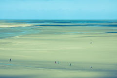 Ocean at low tide under blue cloudy sky, at Mont Saint Michelle Royalty Free Stock Photography