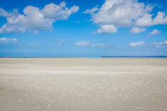 Ocean at low tide under blue cloudy sky, at Mont Saint Michelle Royalty Free Stock Image