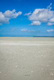 Ocean at low tide under blue cloudy sky, at Mont Saint Michelle Stock Photo