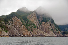 Ocean Monoliths in the Fog. Coastal Rocks in the fog in Kenai Fjords in Alaska royalty free stock image