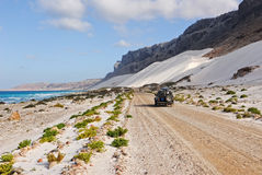 Ocean, mountain, white dune and car Royalty Free Stock Image