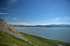 Ocean and mountains. Colors, green grass, stone cliffs, blue sky, low clouds, resting, visiting the United Kingdom, a great place to vacation, sandy beach Stock Photos