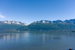 The ocean and mountains in valdez. A calm ocean with the tide waning at a port in alaska Stock Photos