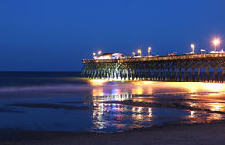 Ocean pier at night. Atlantic ocean pier with bright lightening during the beautiful summer night. Surfside Beach, Myrtle Beach area, South Carolina, USA Royalty Free Stock Images