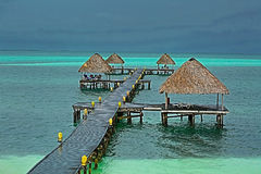 Ocean pier standing in the green emerald water with beach shed attached Stock Photography