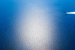 Ocean and the Plane. Over the ocean with a plane and visible wing in a sky royalty free stock photography