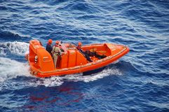 Ocean rescue operation. Training ecercise to rescue man overboard in bright orange vessel royalty free stock image