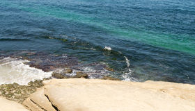 Ocean ripples near rocky shoreline Royalty Free Stock Photos