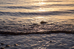Ocean ripples at the sunset Stock Images