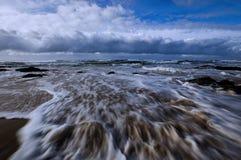 Ocean river. Rising tide streams over sandy beachline Stock Photography