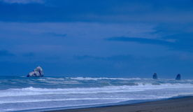 Ocean and rock formations along the Oregon coast. Panoramic and dramatic view of incoming waves and rock formations in the ocean on the Oregon coast Royalty Free Stock Image