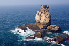Ocean rocks. Huge rocks and cliffs extending to the blue ocean and populated with sea birds. Nau dos Corvos, Peniche, Portugal Stock Images
