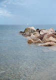 Ocean rocks. In the water with the white yacht on the horizon Royalty Free Stock Images