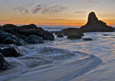 Ocean rocks at sunset. Ocean rocks with glowing sunset sky in the background Stock Photos