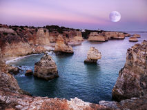 Ocean Rocky Coastline, Night Sky Full-Moon. Islets and ocean rocky coast at night full-moon light. Fantasy landscape background. Lagos Portugal Stock Photo