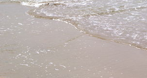 Ocean rolling in over the sand stock footage