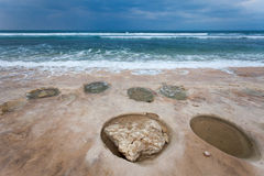 Ocean with round craters on the shore. Tropical ocean with cloudy sky and with a round craters on the shore Stock Photos