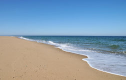 Ocean's Edge. Waves from the receding tide lap the sand at Race Beach on Cape Cod stock photo