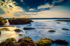 The ocean's gentle tides. A gentle tides plays in and out of the rocky coastline while the sun sets stock photo
