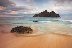 Ocean's Movement. The beach of Calheta in Porto Santo Island, Madeira, Portugal with da Cal islet in the background Royalty Free Stock Photo