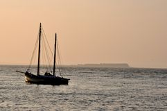 Ocean and sail boat at sunrise Stock Photo