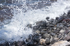 Ocean Spray on Rocks Closeup. Close up frame freezes the water spray of wave action on shoreline rocks. The splashing wave action moved the beach pebbles to make Royalty Free Stock Image