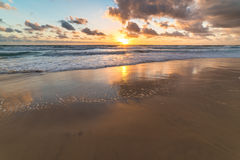 Ocean sandy shore with soft waves against sunrise sky on the bac Stock Images