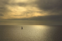Ocean sea sunset view and black sail boat. Mediterranean sea. It Stock Photos
