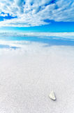 White rock in a white beach under blue and cloudy sky Stock Photos