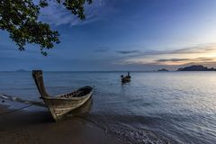 Ocean seashore with island and boat on water at sunset in Krabi, Thailand Royalty Free Stock Images