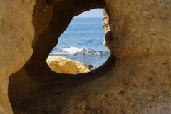 Ocean seen through hole in rock Royalty Free Stock Images