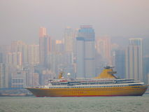 Ocean Ship in Front of Hong Kong Skyline. An ocean cruise ship in front of the Hong Kong skyline as it leaves Victoria Harbour Stock Photo