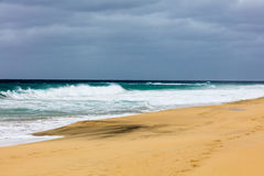 Ocean shore with sandy beach and waves. On a cloudy day. Footprints in send Stock Images