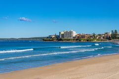Ocean shoreline with sandy beach and waterfront houses Stock Images