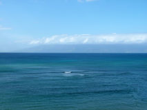 Ocean and Sky. View of an ocean against blue sky with land and cloud in the background Stock Image