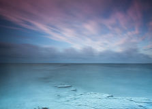 Ocean and Sky. Slow shutter of ocean and sky showing pink clouds and glassy ocean Royalty Free Stock Photos