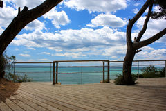 Ocean sky view. Modern Mediterranean terrace on the sea with ocean blue sky view clouds and trees and a chrome metal balustrade royalty free stock image