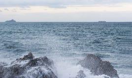 Ocean splash with foam near big rocks. Ocean splash and white foam near big rocks stock photo